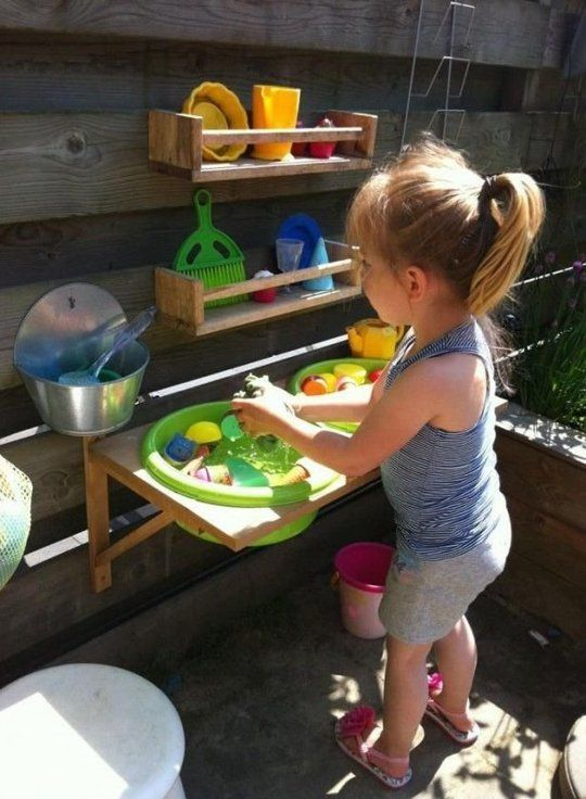 a colorful outdoor kitchen with wooden shelves, colorful plastic tableware and toys for having fun