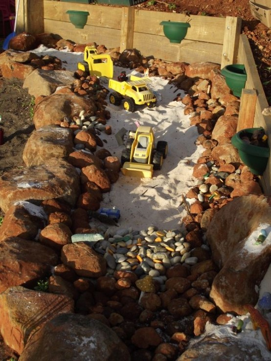 an old pond or fountain space can be transformed into a playground with sand and pebbles - a building or some other one that your kids may need
