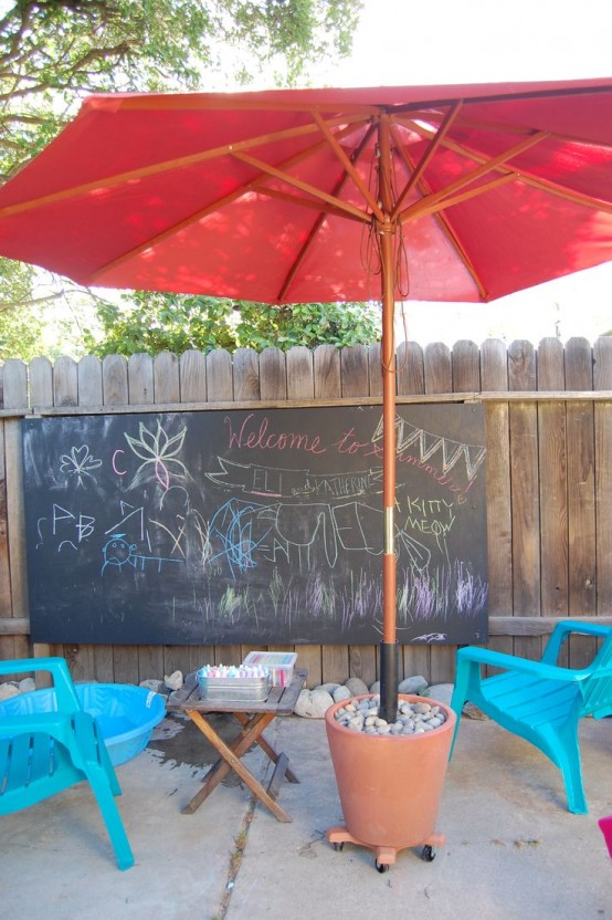 a chalkboard, colorful chalk, bright chairs, a red umbrella is a cool kids' creativity nook - and not only for kids