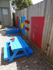 a colorful outdoor space with a blue dining set, colorful chalkboards and a blue sand box with various stuff for playing