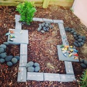 a small playground with pebbles, stepping stones, colorful little toy cars is a cool and cozy nook to play in