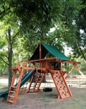 a cool outdoor sports ground with climbing walls, ladders, a tyre swing and a small tree house up there