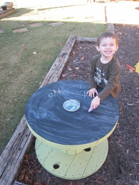 a wooden chalkboard table and colorful chalk is great for creativity and art outdoors