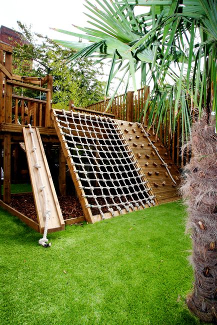 a small outdoor playground with green lawn, ladders, nets, a small tree house and a sand box under it