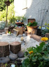 a fun and cute outdoor playground with plants, stumps, sand, pebbles, blooms and some garden figurines