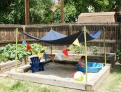 a simple outdoor sand box with a canopy, colorful buntings, balls and a plastic bathtub is a perfect idea for your garden