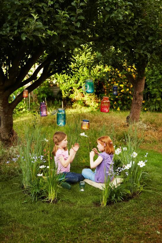 a bright play nook outdoors with blooms, green lawn and colorful candle lanterns hanging down from the tree