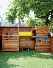 a simple sports ground of wood, with a green lawn, climbing walls and a space to play pirates