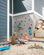 a creative outdoor play space wiht a climbing wall and a sand box with colorful toys