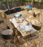 a simple rustic place space with a sand box, a wooden table and tree stump stools plus some metal tableware to play with