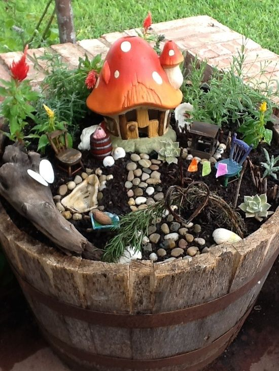 a little fairy garden of a wooden bucket, some plants and blooms and a mushroom house - add some tiny dolls and let your kids play with them