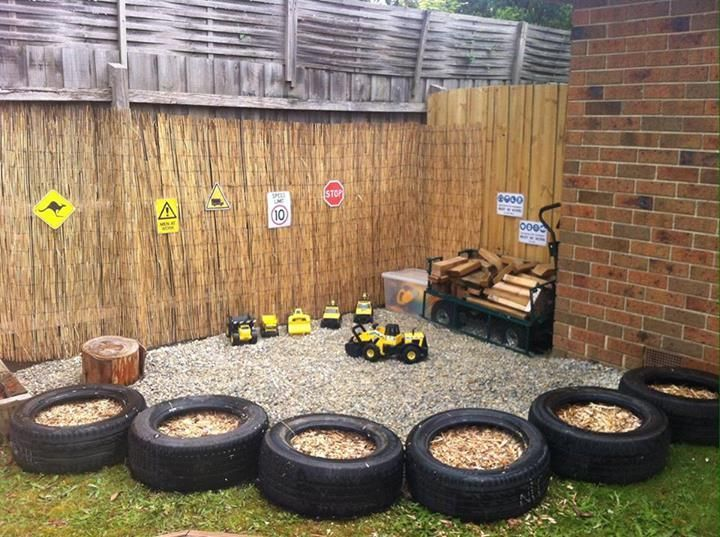 a simple playground with lots of toy cars, signs, wood is lined up with old tyres filled with sand