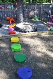 a colorful playground with bright buntings, colorful tree stumps as stepping stones, a small sand box of a giant tyre