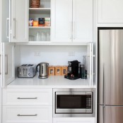 a cabinet with folding doors, a coffee machine, a kettel and a toaster plus mugs and sugar is a perfect breakfast station