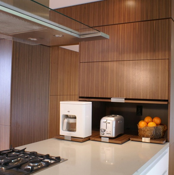a sleek cabinet with retracting shelves and appliances and fruits in a bowl for a minimalist kitchen