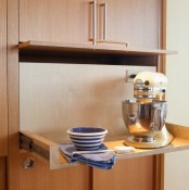 a cabinet with a retracting shelf, a mixer and a bowl helps to hide pieces that you need only from time to time