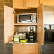 a light stained plywood cabient with several appliances and a retractable shelf is a very comfy idea to make your kitchen look neat