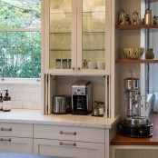 a glass cabinet with a lower part with a folding door and a coffee machine and toaster hidden here to keep the kitchen decluttered