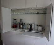 a white cabinet with a glass and retractable shelves and several different appliances is a real cooking and coffee station