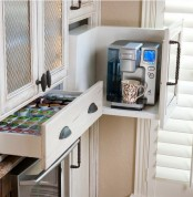 a large drawer with a removed part holds a coffee machine and a drawer next to it holds everything you may need for a coffee