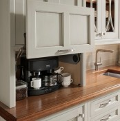a storage cabinet with a retractable door and a mini coffee station inside, with coffee and a coffee machine