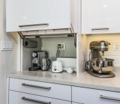 a white cabinet with a coffee machine, a kettle, a toaster and some other appliances is a cool idea to store your stuff without cluttering the space