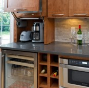 a mni cabinet with a retracting door and a couple of appliances inside is a creative idea for storage