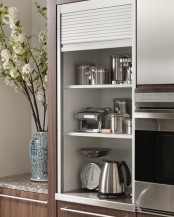 a narrow cabinet with shelves holding cookware, pots, some appliances can be closed with a shutter