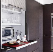 a large cabinet with a shutter cover and usual and retractable shelves with appliances and a microwave allows serving breakfast here