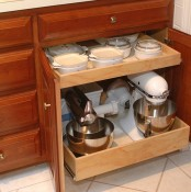 a rich stained lower cabinet with retractable shelves that hold appliances, pots and bowls is a cool idea to declutter the space