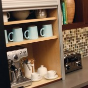 a storage cabinet with a coffee machine, mugs and cups and sugar is a mini coffee station with a shutter sliding down
