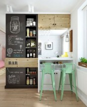 a farmhouse kitchen in white, a chalkboard cabinet for storing various stuff and make notes about this stuff plus green metal stools
