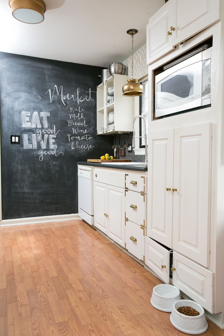 a neutral farmhouse kitchen with a chalkboard accent wall, metallic pendant lamps and dark countertops