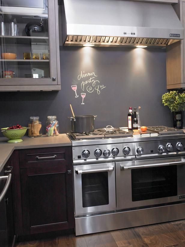 a dark kitchen with purple lower cabinets and grey upper ones, a chalkboard backsplash and lights over the cooker is very chic
