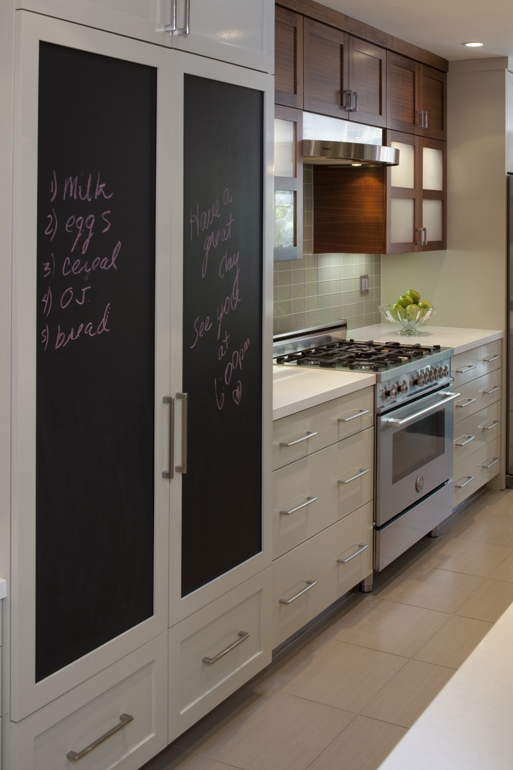 a neutral kitchen with a large storage piece with chalkboard doors that cozies up and relaxes the decor of the space