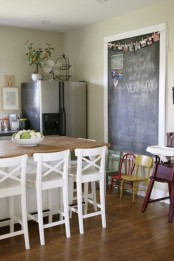 a farmhouse eat-in kitchen with a large chalkboard for making notes and creating art there is very welcoming