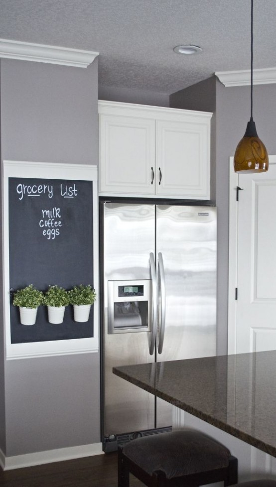 a chalkboard in a frame with some greenery is a lovely grocery list to rock in any kitchen