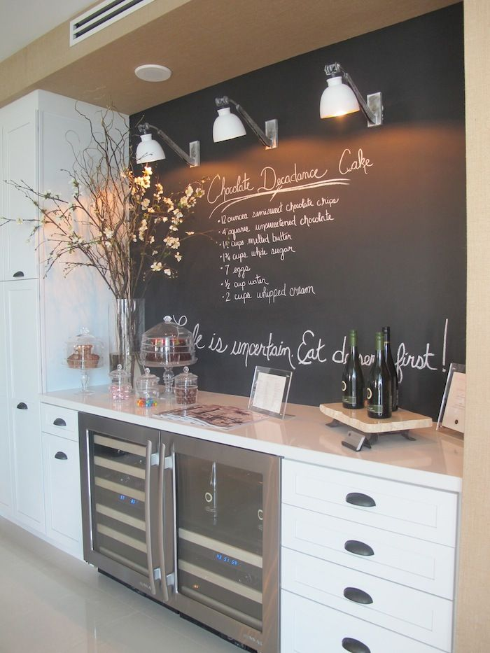 a Scandinavian kitchen with a chalkboard accent wall and backsplash in one, it contrasts the cabinets and is very practical in use