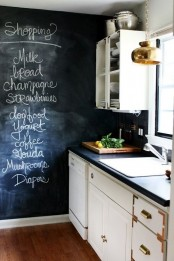 a welcoming farmhouse kitchen with neutral cabinets, a chalkboard accent wall, pendant lamps and black stone countertops