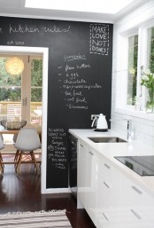 a sleek white kitchen and an accent chalkboard wall that can be used for practical purposes and adds a contrasting touch