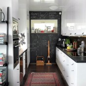 a farmhouse kitchen with white cabinets, black stone countertops, a statement chalkboard wall and windows for more light