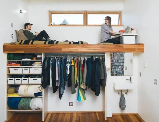 an open closet with hangers, boxes and open shelves and a platform with a home office and a daybed on top