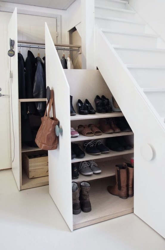 a whole closet and shoe storage hidden in the staircase drawers is a very functional idea that saves lots of space
