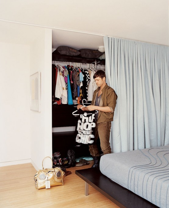 a closet with lots of shelves and a holder for clothes hangers can be hidden with a curtain and it declutters your space and doesn't make you make a separate closet room