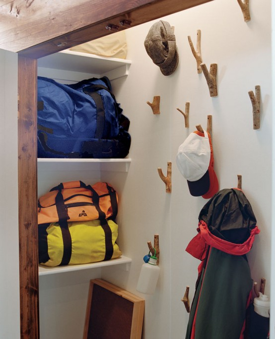 a closet with hooks on the wall that let hanging clothes, bags and other stuff and not to take any shelf and floor space for that