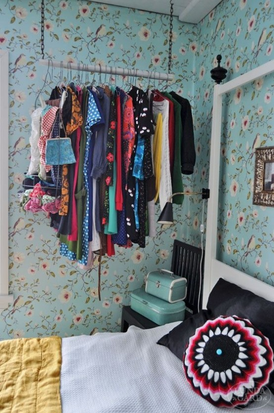 a chain and wood stick closet with clothes hangers is a non-bulky and airy idea that makes clothes part of decor