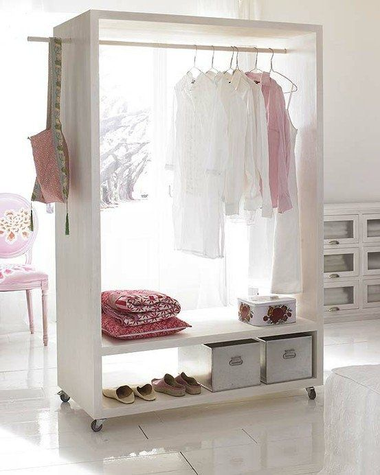 an open closet on casters features boxes, clothes hangers and can be moved anywhere you want it