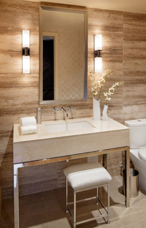 small and elegant wall lamps accent the mirror and make using it more comfortable at the same time