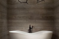 a statement chandelier in black with candle-like lights is a stylish idea to accent a modern bathroom