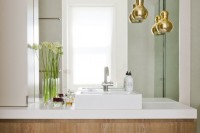 gold shaped pendant lamps accent the bathroom giving it a chic look and a timeless feel as metallics are timeless